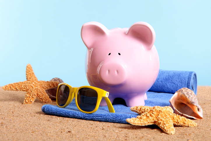 Pink piggy bank on a beach with sunglasses and beach towel.