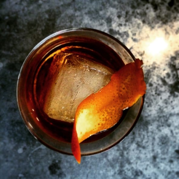 Overhead shot of craft whiskey cocktail on marble bar