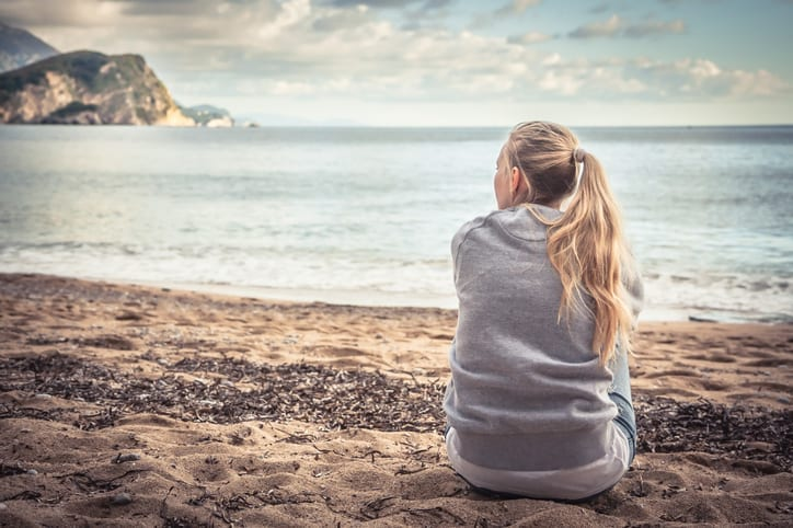 Pensive lonely young woman tourist sitting on beach hugging her knees and looking into the distance with hope