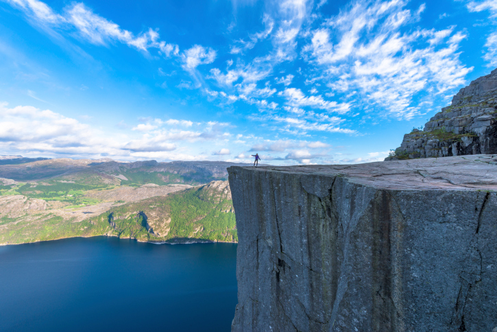 Tourist standing on Famous Pulpit Rock in Norway